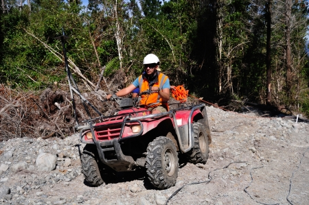 seismic: Men use an all terrain vehicle for setting out cables in a seismic reflective survey