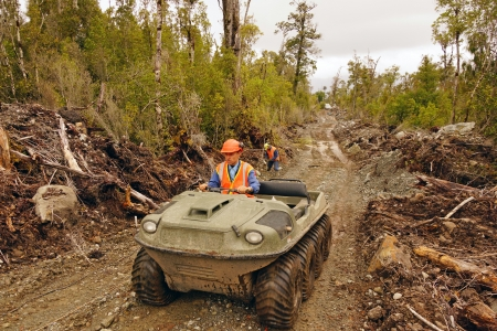 seismic: Men travel in an all terrain vehicle while setting out cables for a seismic reflective survey on the West Coast of New Zealand