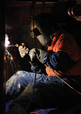 Welder joining pipes together for an exploratory gas well photo