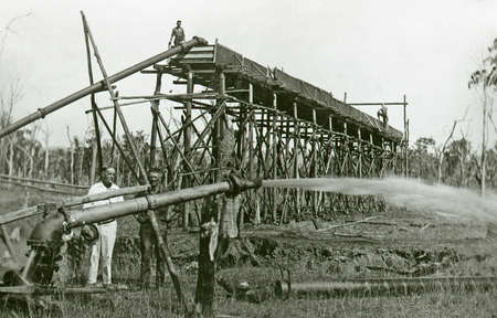 alluvial: QUEENSLAND, AUSTRALIA, CIRCA 1870: Unidentified men work a sluice gun to wash alluvial gold from gravel  in the late 1800s, probably near Gympie in Queensland, Australia. Sluicing was a popular way to extract gold.
