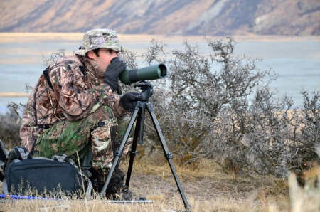 hunters: Hunter scoping for Himalayan tahr in the Southern Alps of New Zealand Stock Photo