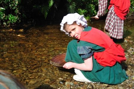 Schulmädchen Goldwaschen auf einer pädagogischen Exkursion