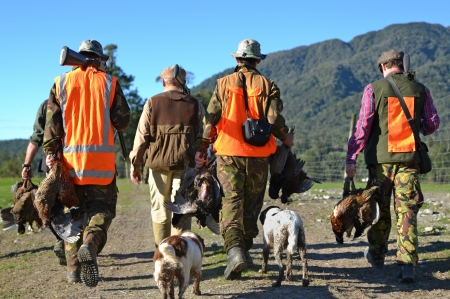 A group of friends return from their pheasant hunt with plenty of game on the West Coast of New Zealand