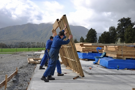 Builders stand up a wall framing section on a large building photo