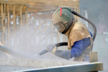 tradesman sandblasting beams for building project Stock Photo