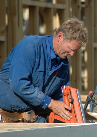 house trained: builder using nail gun on building site
