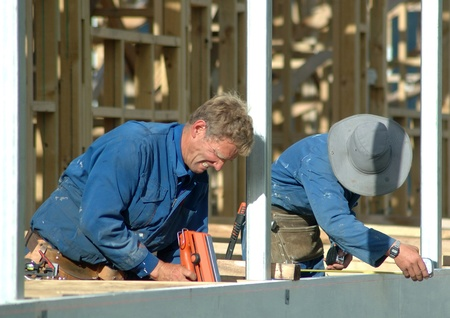 builder using nail gun on building site while colleague measures up Stock Photo