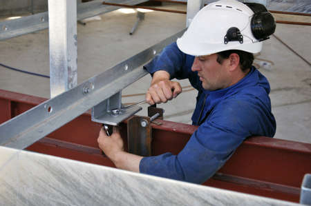 dairying: Builder bolting together the rotary platform in a new dairy