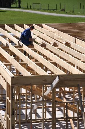 works: builder working on first floor framework on building
