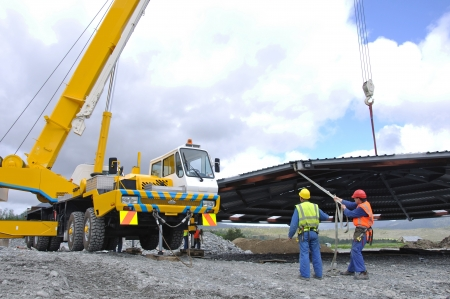 A 70 tonne crane lifts the roof onto a new dairy, Westland, New Zealand photo