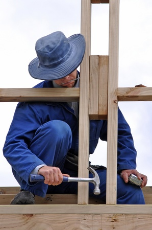 house trained: builder using hammer to nail off framework on building Stock Photo