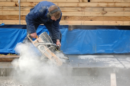 Builder cuts edge of concrete slab with diamond saw blade concrete cutter Stok Fotoğraf - 20020243