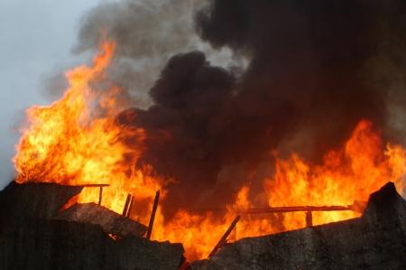 vlammen en rook opstijgen uit brandende gebouw Stockfoto