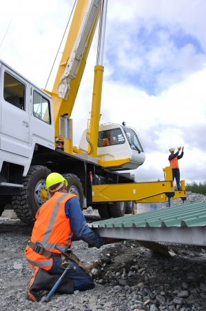 westland: Builder gives directions to crane driver and other men lifting the roof onto a new dairy, Westland, New Zealand Stock Photo