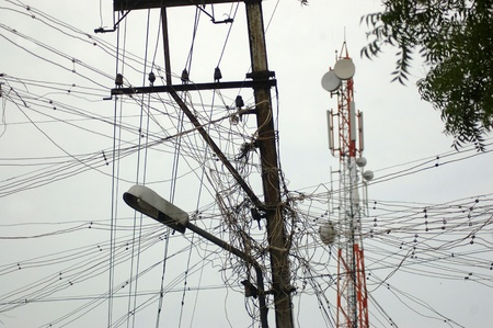 electricity supply: Typical electricity supply in India with communications tower in background Stock Photo
