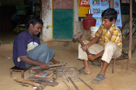 TAMIL NADU, INDIA, circa 2009: Unidentified man and his son hammer out steel in a blacksmith's shop, circa 2009 in Tamil Nadu, India. Much of India's economy still relies on hand tools and skilled tradesmen.