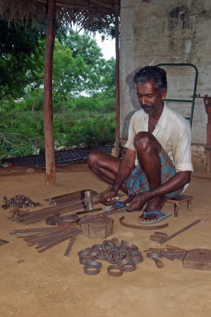 TAMIL NADU, INDIA, circa 2009: Unidentified man hammers out steel in his blacksmiths shop, circa 2009 in Tamil Nadu, India. Must of Indias economy still relies on hand tools and skilled tradesmen.