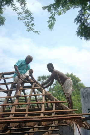 relies: TAMIL NADU, INDIA, circa 2009: Carpenters working on a roof circa 2009 in Tamil Nadu, India. Much of Indias economy still relies on hand tools and skilled tradesmen.