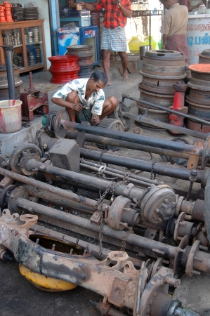 relies: TAMIL NADU, INDIA, circa 2009: Unidentified man working on axles in a city street, circa 2009 in Tamil Nadu, India. Much of Indias economy still relies on hand tools and skilled tradesmen.