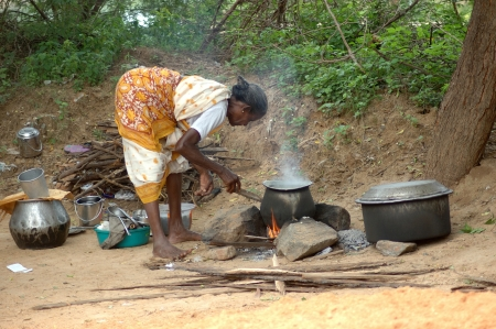 TAMIL NADU, INDIA, circa 2009: Unidentified woman cooking rice outdoors, circa 2009 in Tamil Nadu, India. Wood is still used as a fuel in many parts of rural India.