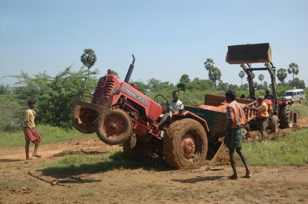 TAMIL NADU, INDIA, circa 2009: Unidentified men work to free a bogged tractor with a load of bricks in the trailer, circa 2009 in Tamil Nadu, India.