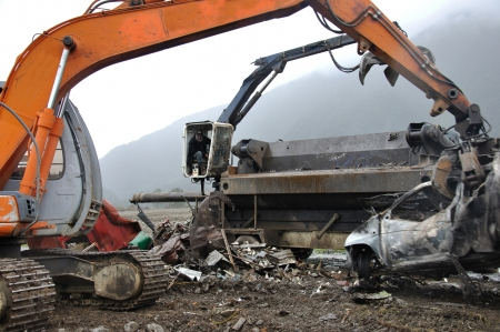 compacting: GREYMOUTH, NEW ZEALAND, AUGUST 12, Unidentified man feeds old vehicles into a steel compacting unit for recycling, on  August 12, 2008 near Greymouth, New Zealand,