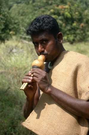 reptillian: TIRUNELVELI, TAMIL NADU, INDIA,  FEBRUARY 28, 2009: Indian man blows whistle to attract snakes on February 28, 2009 in Tamil Nadu, South India. Snakes are released in a protected area. Editorial