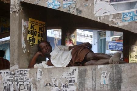 destitute: TAMIL NADU, INDIA, circa 2009: Unidentified man rests on the supports of the main bridge in Tirunelveli, Tamil Nadu, South India. Editorial