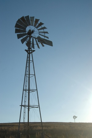 windmills silhouetted against blue sky in barren paddock, Queensland, Australia. Windmills are commonly used for pumping water from bores or dams to troughs for livestock. photo