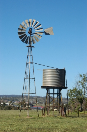 Windmill and tankstand in paddock, Queensland, Australia. Windmills are commonly used for pumping water from bores or dams to troughs for livestock.