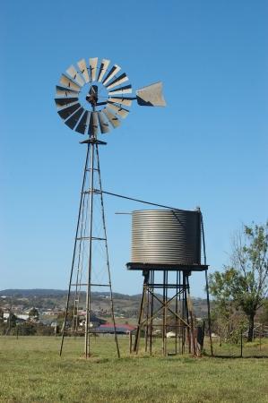 Windmolen en tankstand in paddock, Queensland, Australië. Windmolens worden vaak gebruikt voor het pompen van water uit boringen of dammen te troggen voor vee.