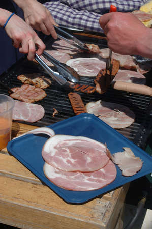 griller: Cooking sausages and ham on a barbecue Stock Photo