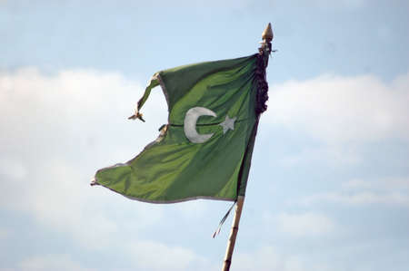 A Moslem flag against blue sky and clouds photo