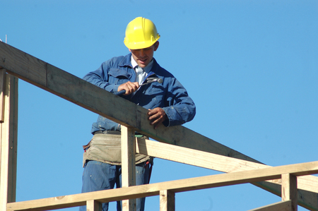 roof framing: builder driving home a nail while finishing the roof framing
