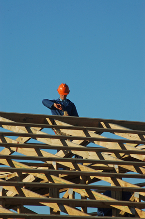 roof framing: builder pulling out a nail while working on the roof framing