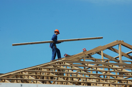 builder carrying timber for the roof framing photo