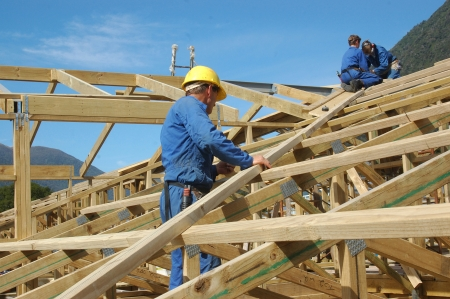 roofing: builders working on the roof of a large house