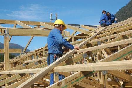 constructeurs travaillant sur le toit d'une grande maison