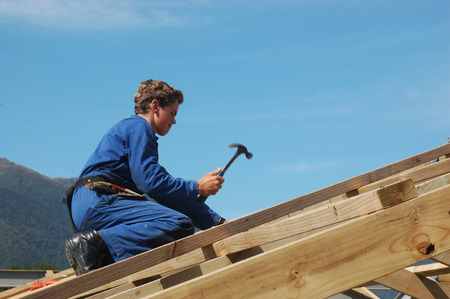 builder driving home a nail while finishing the roof framing photo