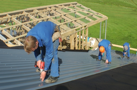builders working on the roof of a large house photo