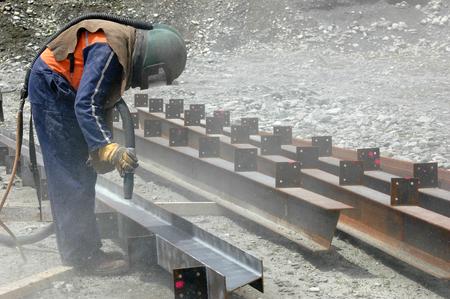 tradesman sandblasting beams for building project photo