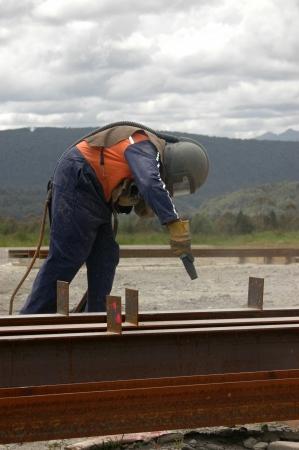 sandblasting: tradesman sandblasting beams for building project Stock Photo