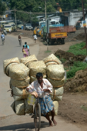 depends: TAMIL NADU, INDIA, circa 2009: An unidentified man and his overloaded bike head to town, circa 2009 in Tamil Nadu, India. The Indian economy depends on private enterprise.
