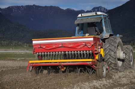dairying: Farmer drilling seed into pasture paddock, Westland, New Zealand