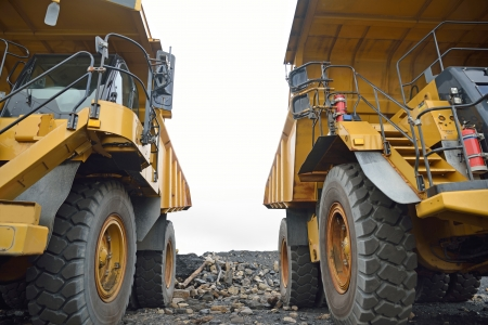 two 130 ton tiptrucks waiting for work at an open cast coal mine, Westland, New Zealand Stock Photo