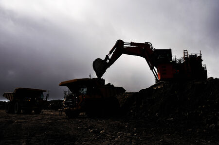 overburden: silhouette of a 190 ton digger loading a 130 ton tiptruck with rock overburden at an open cast coal mine