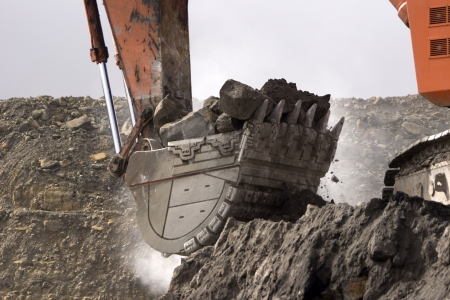 190 ton digger picks up a load of rock overburden at an open cast coal mine, Westland, New Zealand