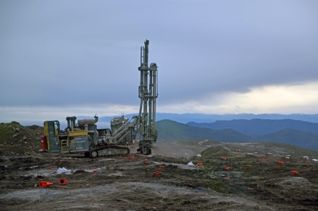 nonrenewable: drilling rig prepares blasting holes to remove overburden at stockton coal mine, Westland, New Zealand