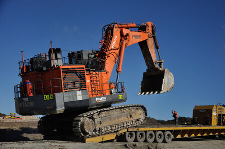 WESTPORT, NEW ZEALAND, AUGUST 31, 2013: Unidentified man directs a 190 ton digger onto a 48 wheel transporter at Stockton coal mine on August 31, 2013 near Westport, New Zealand. Stockton is the countrys largest open cast coal mine.