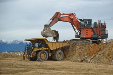 overburden: WESTPORT, NEW ZEALAND, AUGUST 31, 2013  190 ton digger loading a 130 ton tiptruck with overburden at an open cast coal mine on August 31, 2013 near Westport, New Zealand